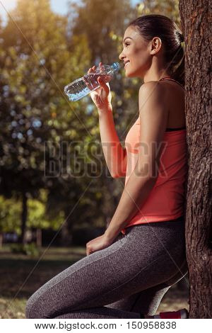 A sip of energy. Young pretty smiling girl wearing sportswear and drinking water while standing in the park after training.
