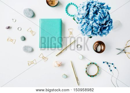 hydrangea feminine accessories mint diary golden clips and pen on white background. top view