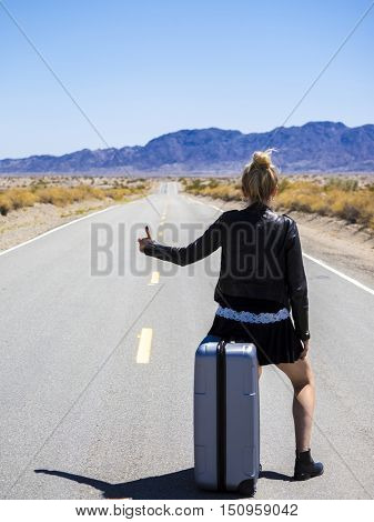 young woman sitting on a suitcase hitchhiking along a desert road
