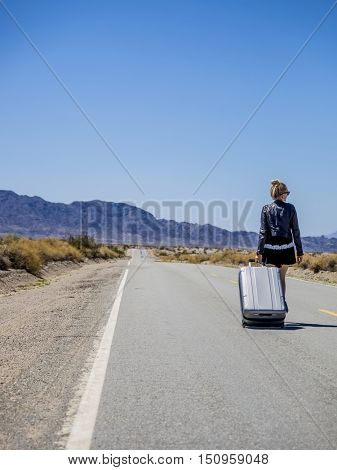 young woman walking with her suitcase on a desert road