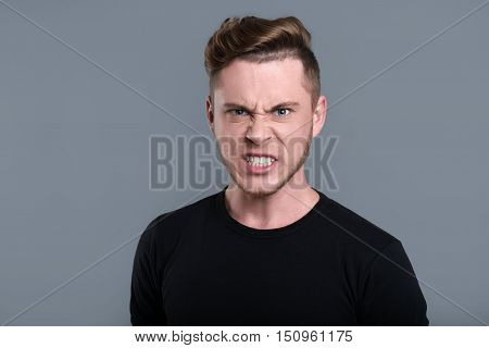 Feeling of anger. Furious bearded young man standing against grey background and looking at you
