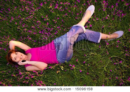 Top view of beautiful young woman lying on the nature and talking at cellphone