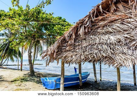 Livingston, Guatemala - August 31 2016: Boat pulled ashore next to palapa on beach at Caribbean town of Livingston