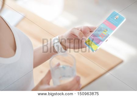 Best way of communication. Pleasant woman holdign smart phone and sending messages while drinking water