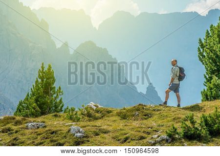 Senior Hiker with Backpack and the Scenic Mountain Vista. Italian Dolomites.