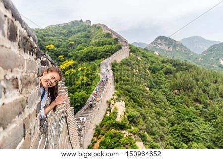 China travel tourist having fun waving hello at the Great Wall in Badaling smiling happy at camera. Woman tourist traveler enjoying her summer vacation holidays in Asia. Multicultural model.