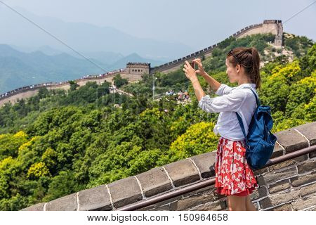 Great Wall of China. Tourist taking photo at famous Badaling during travel vacation holidays at Chinese tourist destination. Woman tourist taking picture using smart phone in Asia.