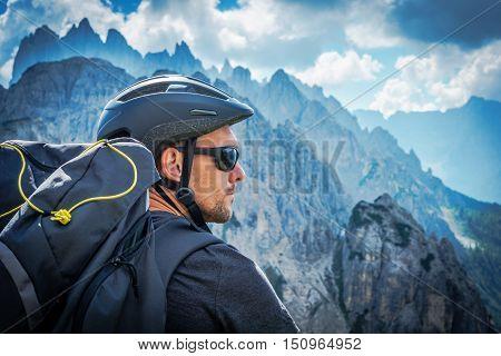 The Mountain Biker in Sunglasses. Caucasian Biker in His 30s Enjoying Fantastic Mountain Vista on the Alps Trail.