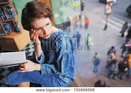 Cute young woman with book in hand sitting in waiting by the window and looking through sunglasses looking to the street
