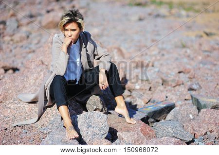 Pensive stylish girl in fashion clothing and bare feet sitting on the stones looking tired.