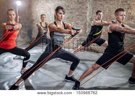 Group of  young people doing workout with elastic band