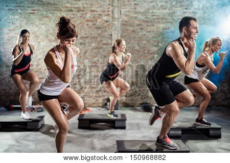 Group training on steppers, healthy, fit people on cardio training