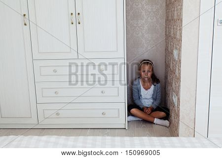 Little aggrieved girl sitting in the corner of her room behind the cupboard
