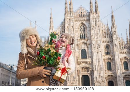 Mother And Daughter With Christmas Tree And Gift In Milan