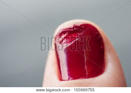 Spoiled red fingernail after manicuring of a woman