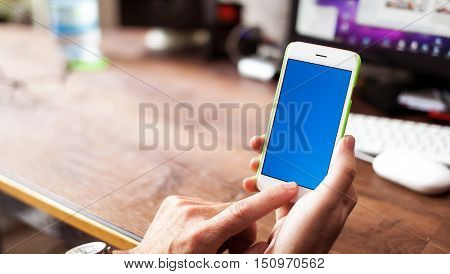 Business Man using Mobile Phone/ Smart Phone in the Office. Typing reading scrolling the touchscreen - blurry background with copy space for text in the display