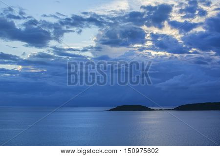 Moody gray storm clouds drift over calm Caribbean Sea and silhouette of tropical island of Isla Culebra