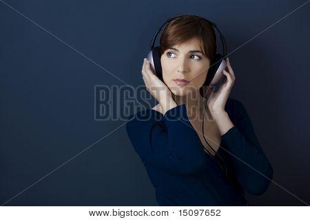 Jovem mulher ouvir música com fones de ouvido sobre uma parede azul