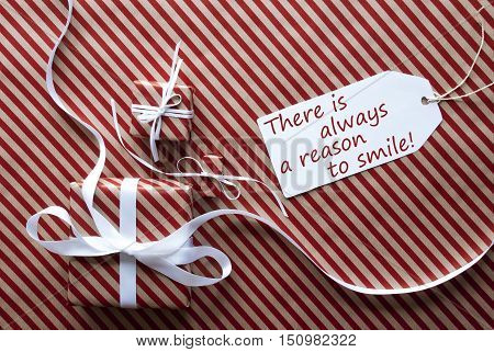 Two Gifts Or Presents With White Ribbon. Red And Brown Striped Wrapping Paper. Christmas Or Greeting Card. Label With English Quote There Is Always A Reason To Smile