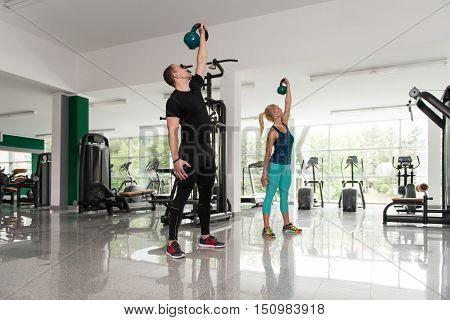 Fitness Couple Using Kettlebells Inside Gym