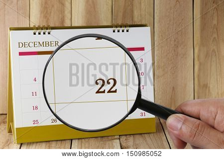 Magnifying glass in hand on calendar you can look Twenty-two date of monthFocus number Twenty-two in DecemberConcept in business and meetings.