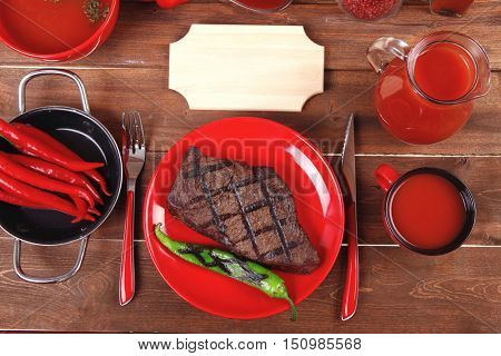 red theme lunch : fresh grilled bbq roast beef steak red plate green chili tomato soup ketchup sauce paprika small jug glass ground pepper american modern cutlery served wooden table empty nameplate