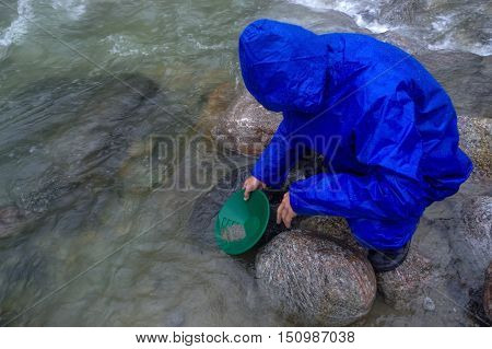 a man panning gold in a river with a sluice box