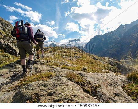 few hikers trekking in alps Switzerland with mountains in the background