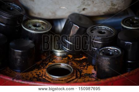 Closeup imageof old oil filters for automobile. Picture of motor oil as product of oil refining industry. Era of internal combustion engines coming to end.