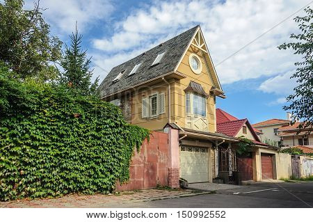 Odessa, Ukraine - August 30, 2016: Small brick single-family two-storied residential house with garage. Sunny summer day.