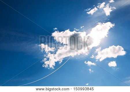 Beautiful fluffy clouds on a blue sky. Vapor trail of Airplane in the sky near the clouds