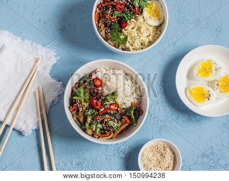 Vegetarian lunch table - rice noodles vegetable stir fry boiled eggs. On a blue background top view