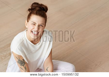 Portrait of playful funny mother sitting at the floor in lotus pose in white clothes. Young Caucasian woman with dense bunch of brown hair making faces grimacing showing teeth in angry manner.