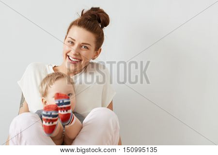 Beautiful Portrait Of Smiling Mother And A Child Sitting Together On The White Background. Happy Eur