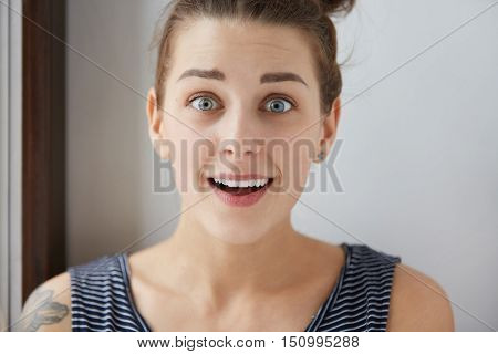 Wondering European Female With Beautiful Blue Eyes And Open Mouth On White Studio Background. Astoni