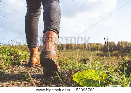 Female legs shod in Hiking boots on the forest background