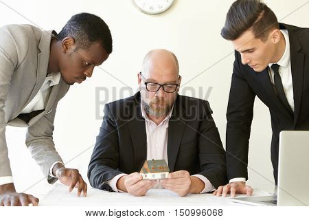 Caucasian Boss In Glasses Holding Scale Model House Of Future Real Estate While Two Young Architects