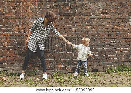 Little Nephew Pulling Her Elder Aunt To Go Further. Young Girl In Checked Shirt, Black Trousers Stan