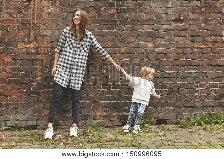 Shot Of Little Blond Boy And Young Girl On A Walk Near Brick Wall. Tiny Kind Pulling Grown-up Aunt T