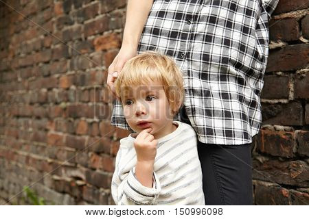 Close-up Portrait Of Little Blond Kid And His Mother Near Brick Wall. Cropped Image Of Pensive Male