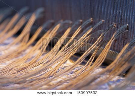 Preparing a loom before starting to make carpets. Warm light and short depth of focus