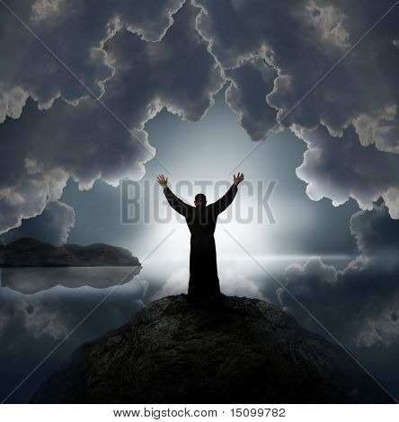 Man holding arms up in praise against  sunset