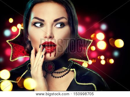 Beauty surprised Halloween Vampire woman over holiday blinking background. Sexy Vampire Girl with dripping blood on her mouth. Halloween Party costume and makeup, Fashion Art design.