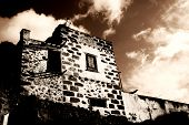 stock photo of hacienda  - Spooky old abandoned hacienda in sepia tones - JPG