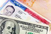 Постер, плакат: Американская виза на странице российского загранпаспорта и доллары США