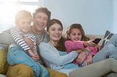 Family watching television while sitting on sofa at home poster