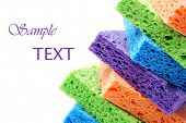 Brightly colored sponges on white background with copy space.