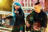 Постер, плакат: Music street performers with girl violinist and man guitarist on cityscape Autumn music street