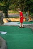 picture of miniature golf  - a little boy putting - JPG
