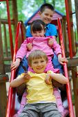 image of threesome  - Children on Slide - JPG
